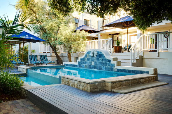 Protea Hotel Dorpshuis swimming pool area with comfortable lounges.